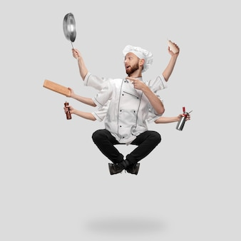 Cuisinière en uniforme multitâche comme shiva isolé sur fond gris studio