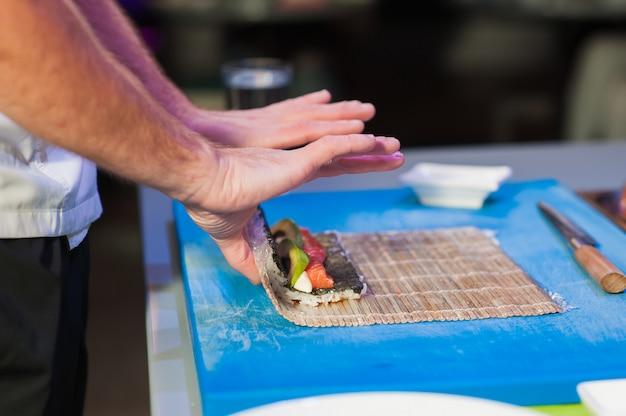 Les cuisiniers mâles préparent des sushis