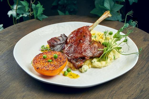 Cuisse de canard confite appétissante avec garniture d'orange grillée et purée de pommes de terre sur une plaque blanche sur une surface en bois