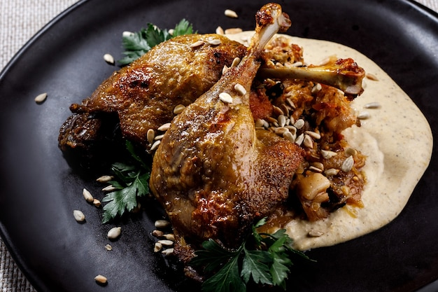 Cuisse de canard à la sauce blanche sur une assiette sombre.