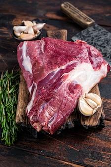 Cuisse de chèvre crue sur planche de boucher avec couperet à viande