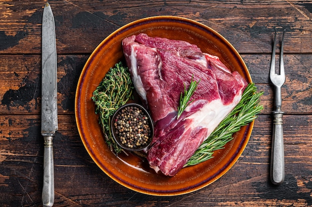 Cuisse ou cuisse de chèvre crue non cuite au romarin et au thym dans une assiette rustique