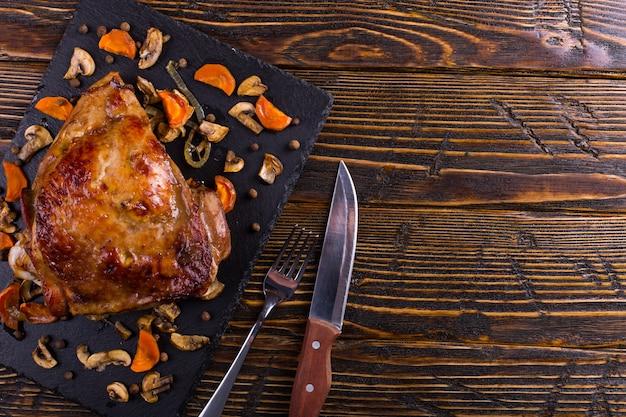 Cuisse de dinde cuite au four avec des épices sur un plateau en pierre noire. la nourriture saine. dîner de thanksgiving.