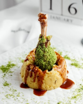 Cuisse de dinde incrustée de pépites vertes disposées verticalement dans une purée de pommes de terre garnie de sauce