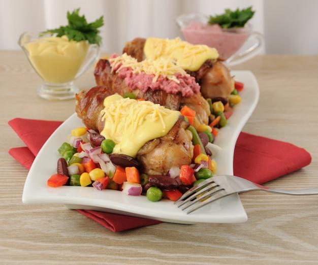 Cuisse de poulet enveloppée de bacon avec des légumes et différentes sauces pour eux