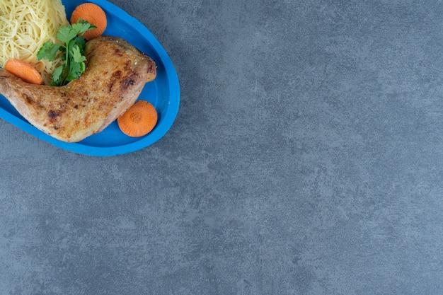 Cuisse de poulet frit et spaghetti sur plaque bleue.