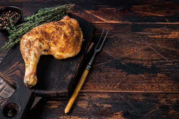 Cuisse de poulet grillé sur une planche de bois