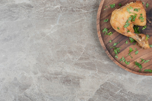 Cuisse de poulet grillé sur plaque en bois.