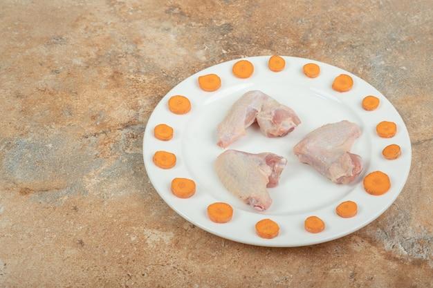 Cuisse de poulet non cuit avec carottes en tranches sur plaque blanche