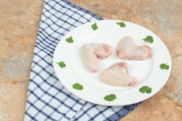 Cuisse de poulet non cuit avec des légumes verts sur plaque blanche