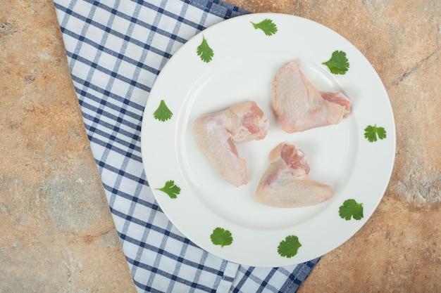 Cuisse de poulet non cuite avec des légumes verts sur une plaque blanche.