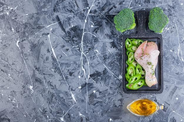 Cuisse de poulet et poivron tranché sur une planche à côté d'huile et de brocoli sur la surface bleue
