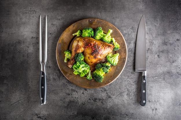 Cuisse de poulet rôti. cuisse de poulet rôtie au brocoli sur table en béton.