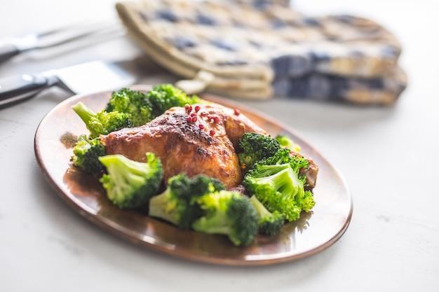 Cuisse de poulet rôti. cuisse de poulet rôtie avec brocoli sur table.