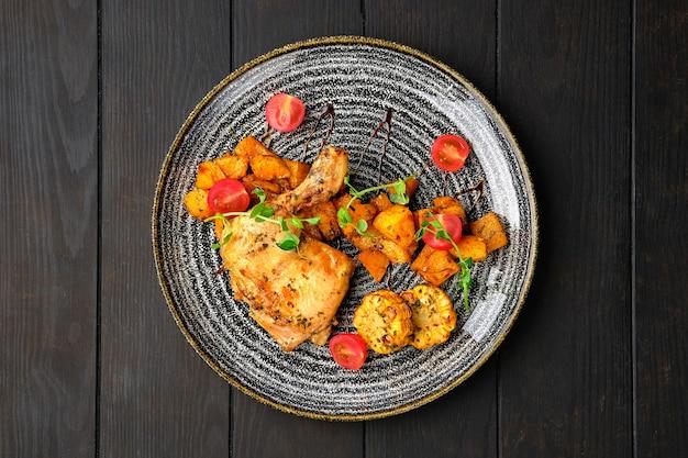 Cuisse de poulet rôtie avec potiron frit, épis de maïs grillé et tomate cerise