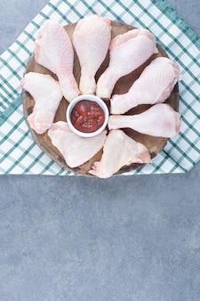 Cuisses et ailes de poulet non cuites sur morceau de bois.