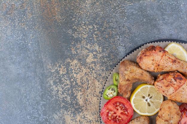 Cuisses et ailes de poulet rôties à bord avec des légumes. photo de haute qualité