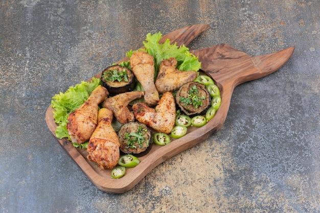Cuisses et ailes de poulet rôties sur planche de bois avec laitue et poivre. photo de haute qualité
