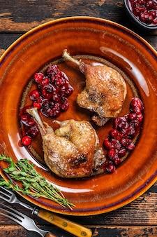Cuisses de canard rôties avec sauce aux canneberges. table en bois sombre. vue de dessus.