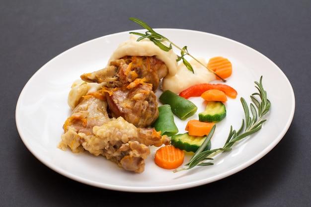 Cuisses de lapin cuites au vin blanc avec sauce béchamel sur une assiette en céramique blanche avec légumes et romarin sur fond noir. viande diététique de lapin cuite au four.