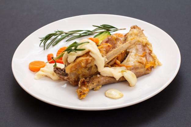 Cuisses de lapin cuites au vin blanc avec sauce béchamel sur une assiette en céramique avec légumes et romarin sur fond noir. viande diététique de lapin cuite au four.