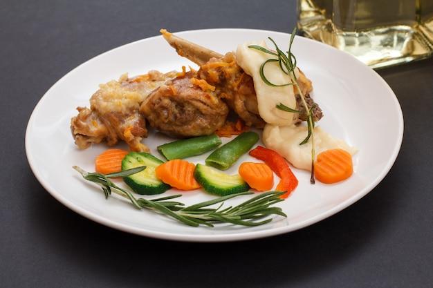Cuisses de lapin cuites au vin blanc avec sauce béchamel sur une assiette en céramique avec légumes et romarin. viande diététique de lapin cuite au four.