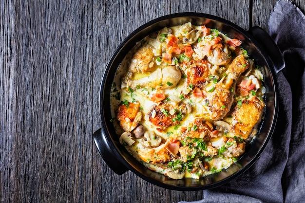 Cuisses et pilons de poulet dans une sauce crémeuse au vin blanc avec moutarde et épices, coq au vin blanc, ragoût de poulet, vue horizontale d'en haut, mise à plat, espace libre