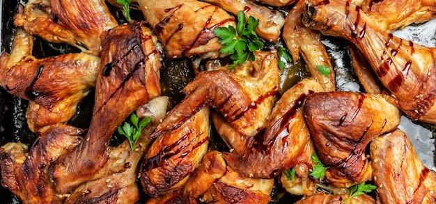 Cuisses de poulet, ailes grillées, frites au four sur plaque de cuisson