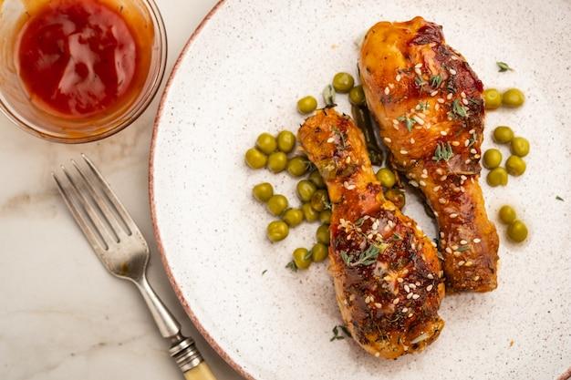 Cuisses de poulet au four avec pois, haricots et herbes fraîches. pilons de poulet avec une savoureuse sauce et des verts