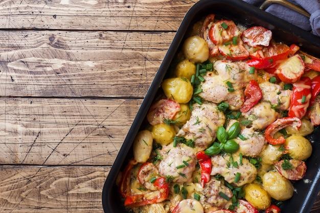 Cuisses de poulet au four, pommes de terre et légumes dans une plaque à pâtisserie sur une table en bois,