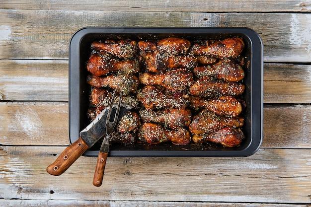 Cuisses de poulet au four avec sauce épicée sur une plaque à pâtisserie