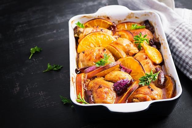 Cuisses de poulet au four. tranches appétissantes de poulet au four avec oignon rouge et oranges dans un plat allant au four.