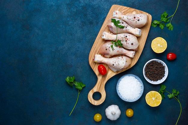 Cuisses de poulet aux épices et sel prêts à cuire sur une planche à découper.