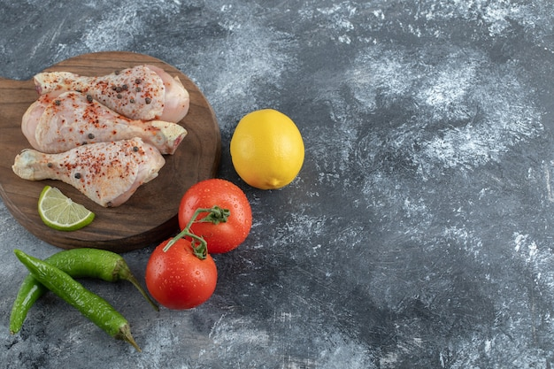 Cuisses de poulet bio crues avec des ingrédients pour la cuisson.