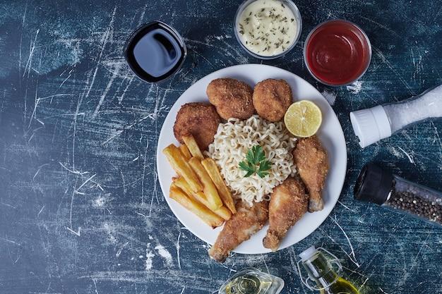 Cuisses de poulet croustillantes avec bâtonnets de pommes de terre et sauces.