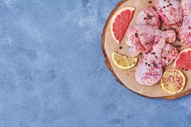 Cuisses de poulet cru aux épices sur une planche de bois sur bleu
