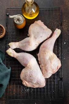 Cuisses de poulet cru aux épices et sel sur fond brun. vue d'en-haut.