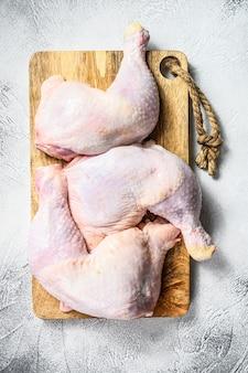 Cuisses de poulet cru frais, cuisses sur une planche à découper