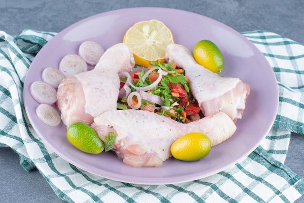 Cuisses de poulet cru avec des légumes sur une assiette violette.