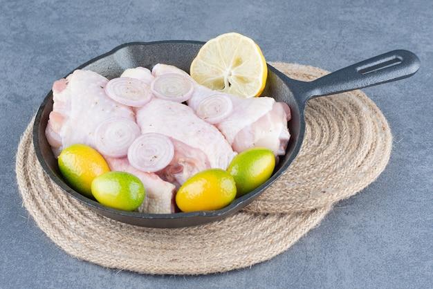 Cuisses de poulet cru avec des légumes sur une poêle noire.