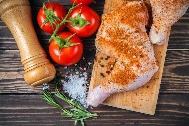 Cuisses de poulet cru sur une planche à découper sur une table en bois