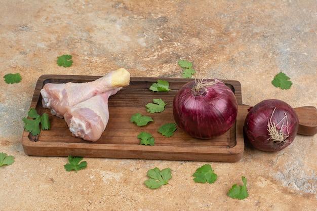 Cuisses de poulet cru avec des verts et des oignons sur une planche à découper en bois