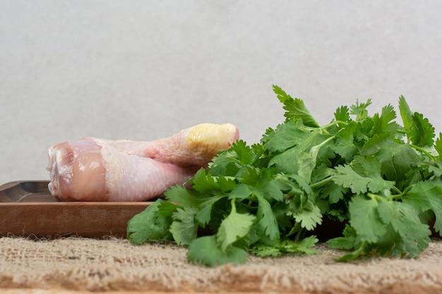 Cuisses de poulet cru avec des verts sur une planche à découper en bois.