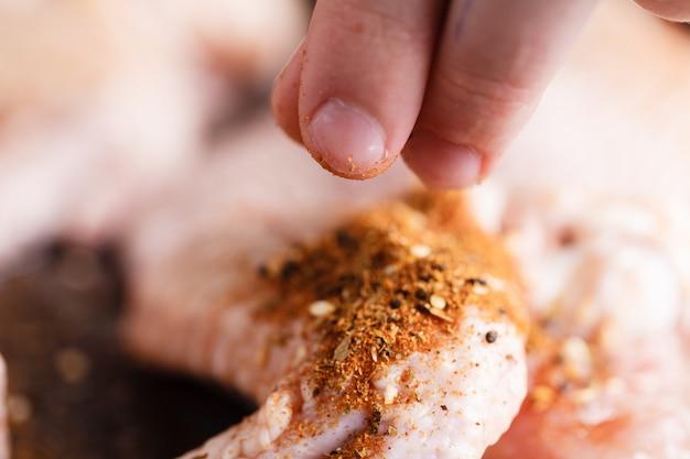 Cuisses de poulet crues au poivre et aux herbes.