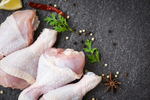 Cuisses de poulet crues aux herbes et épices au piment citron et aux champignons sur la vue de dessus de plaque noire, viande de poulet crue crue marinée avec des ingrédients pour la cuisson