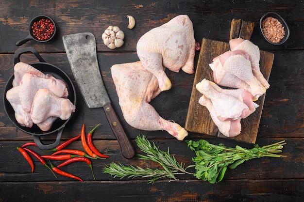 Cuisses de poulet crues crues, pilons, ensemble et vieux couteau couperet de boucher, avec assaisonnement et herbes romarin et thym, sur la vieille table en bois sombre, vue de dessus à plat