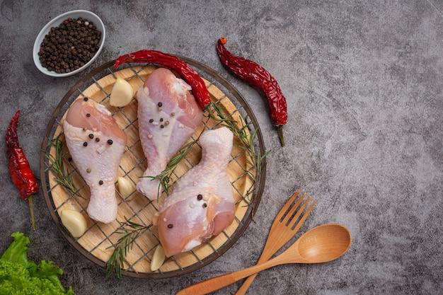 Cuisses de poulet crues crues sur la surface sombre.