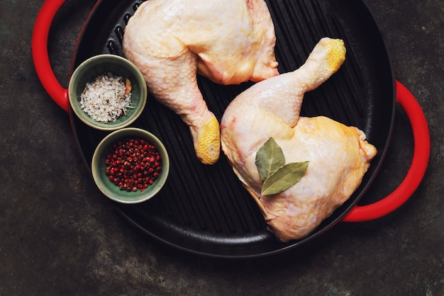 Cuisses de poulet crues dans la poêle en fonte sur fond de métal rustique. concept d'aliments crus. vue de dessus. mise à plat