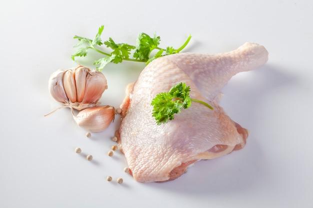 Cuisses de poulet crues avec des épices et des légumes sur un fond blanc