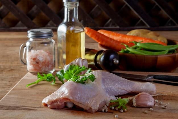 Cuisses de poulet crues avec des épices et des légumes sur une planche de bois